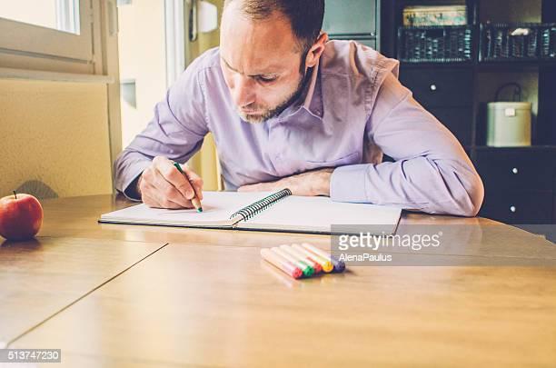 Adulte des livres de coloriage-jeune homme se détendre à la maison