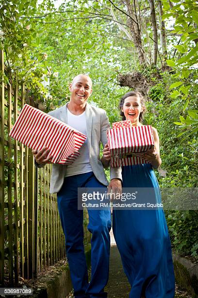 Adult couple carrying birthday gifts along garden path for surprise party