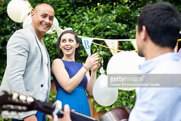 Adult couple dancing and clapping at garden birthday party