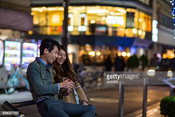 Adult couple looking at something on a smartphone phone together