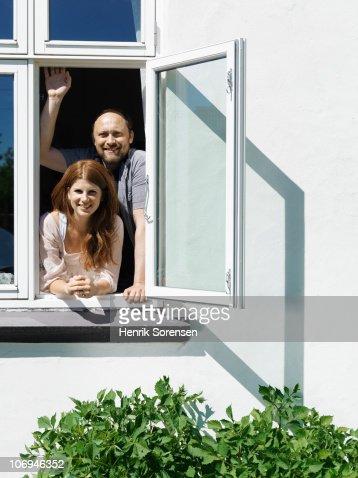 Adult couple looking through open window : Stock Photo