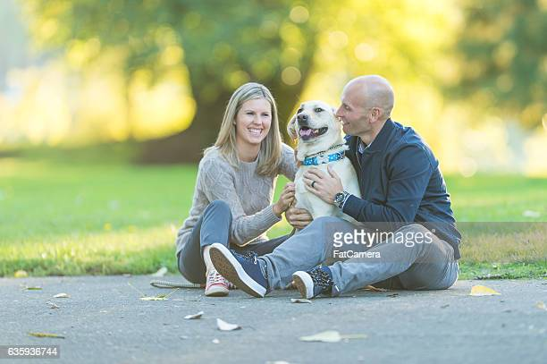 Adult couple playing with their dog in a park on a