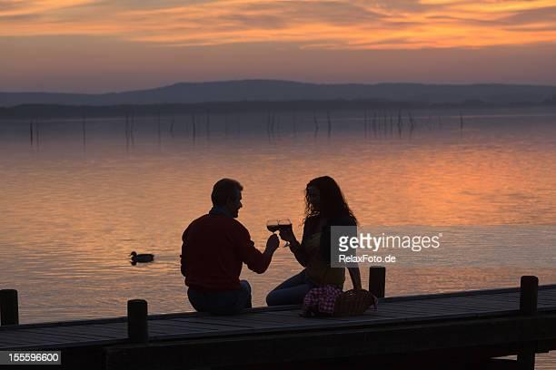 Adulte couple assis sur la jetée de boire du vin, au coucher du soleil