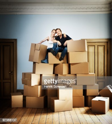 Adult couple sitting on top of moving crates mount : Stock Photo