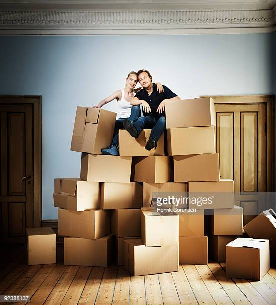 Adult couple sitting on top of moving crates mount