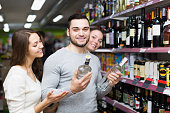 Adult happy customers choosing vodka at strong drinks shelf