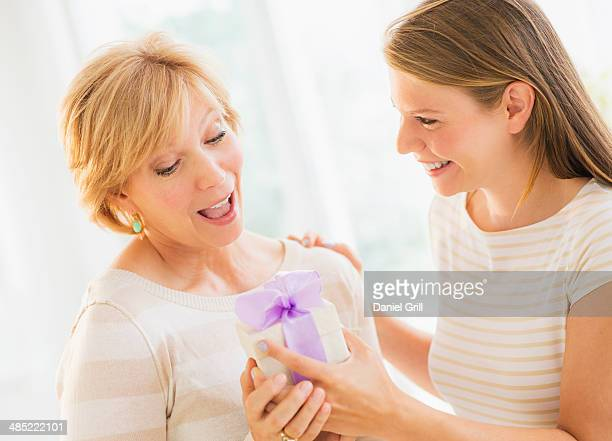 Adult daughter giving present to mother