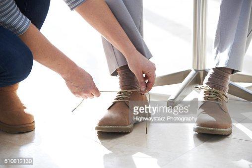 Adult Daughter Helping Senior Tie Shoelaces : Stock Photo
