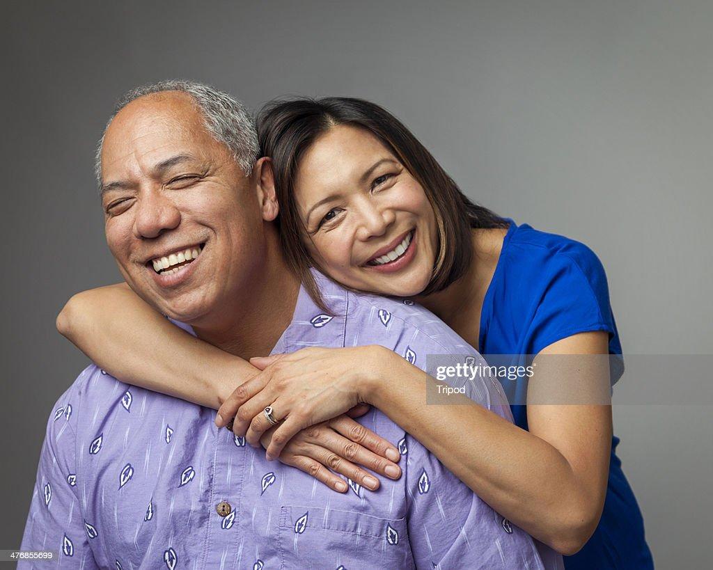 Adult daughter hugging mature father, smiling