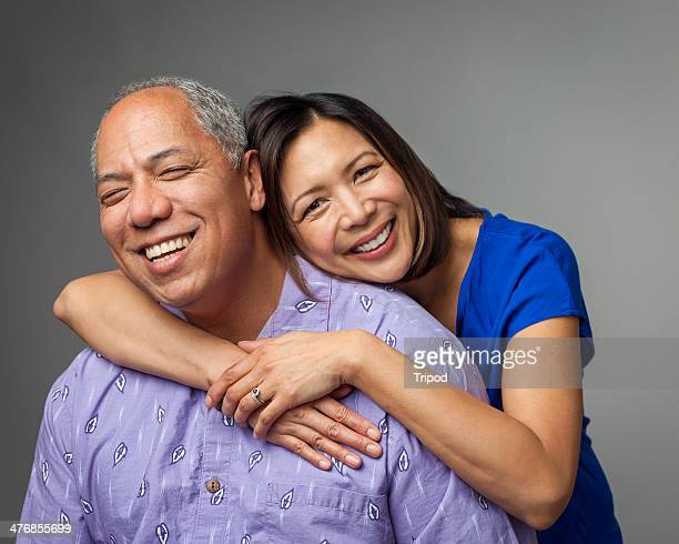 Adult daughter hugging mature father, smiling