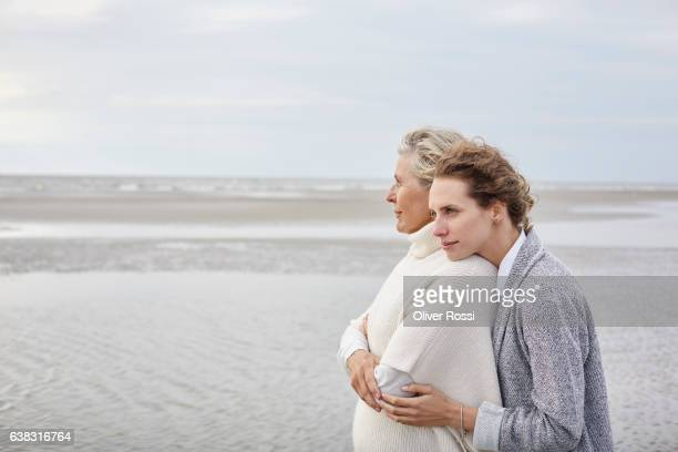 Adult daughter hugging mother on the beach