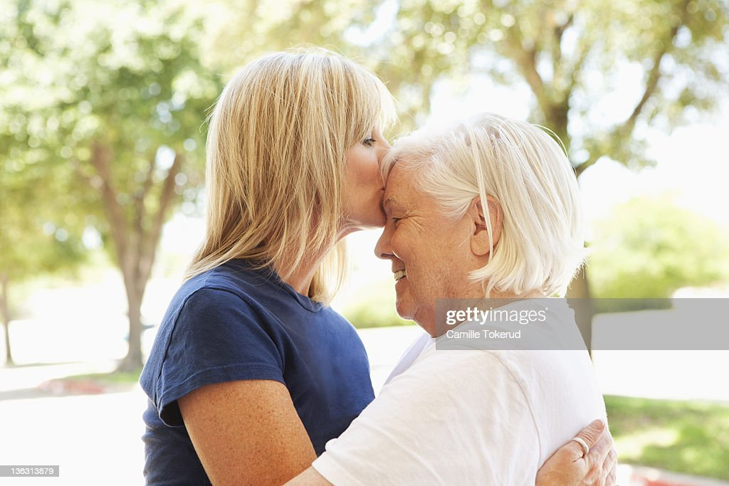 Adult Daughter kissing mother on her forehead