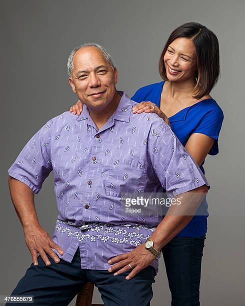 Adult daughter standing behind mature man, smiling
