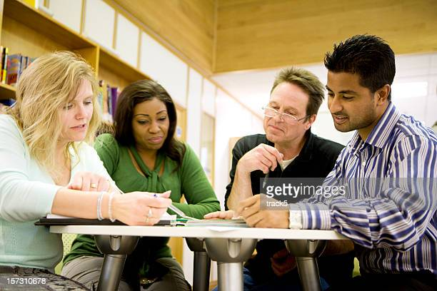 adult education: Diverse mature students working in their college library