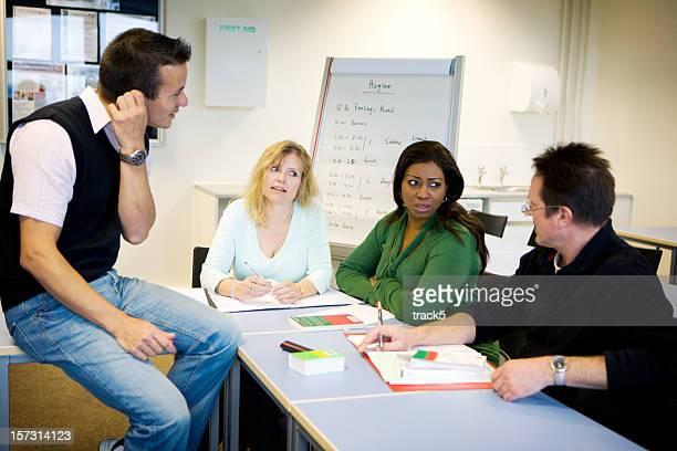 Formation des adultes: Étudiants matures débat en cours avec leur professeur