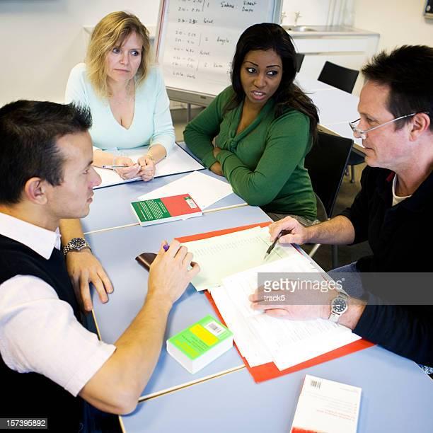 Formation des adultes: Étudiants adultes travaillant ensemble dans une réunion d'équipe