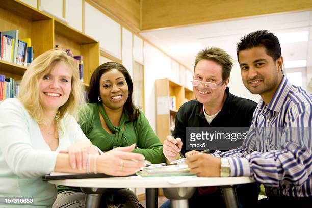 adult education: smiling diverse group of mature students working together