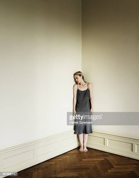 Adult female against corner in empty room