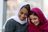 Two (2) attractive muslim adult female friends smile as they walk through the city. In this close-up, they are stylish and enjoying a cold winter stroll together.