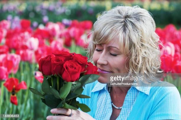 Donna adulta tenendo petali di rose