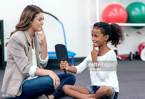 Adult female speech therapist helping african american girl