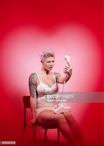 adult female talking on phone with pink backdrop