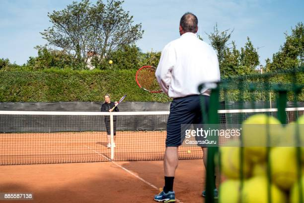 Adult Female Tennis Player Training with her Coach