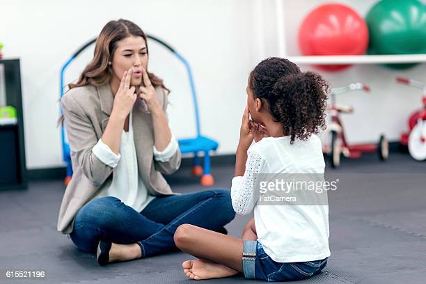 Adult female therapist guiding young girl in speech therapy