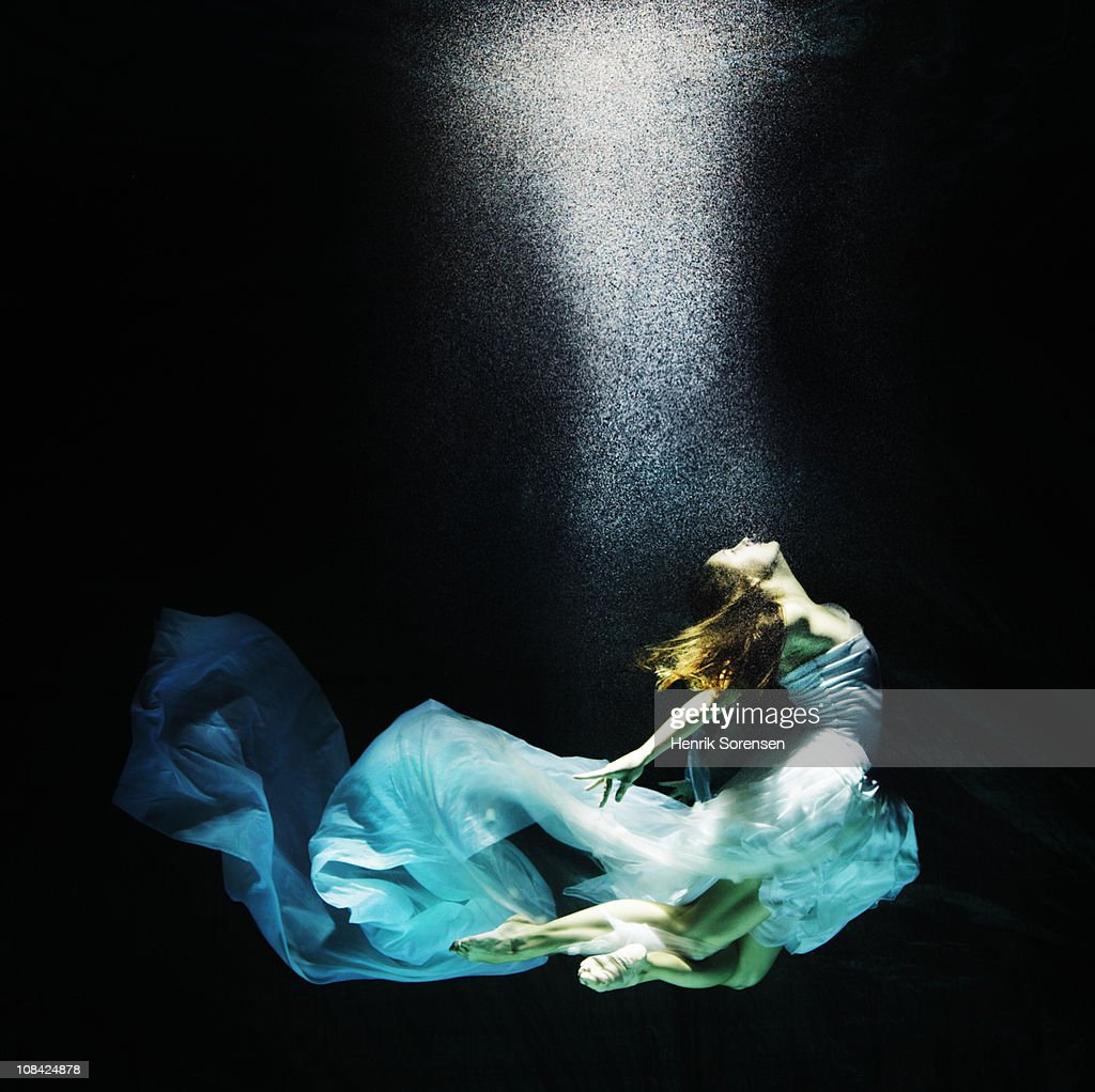 Adult female under water in flowing evening dress : Stock Photo