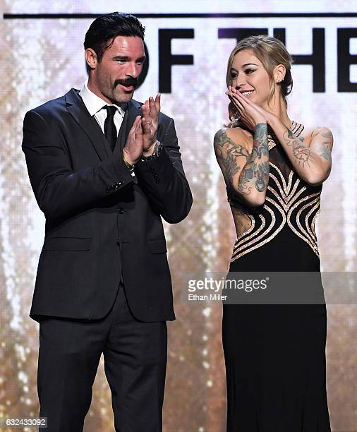Adult film actor Charles Dera and adult film actress Kleio Valentien clap on stage as they accept the award for Movie of the Year for 'Suicide Squad...