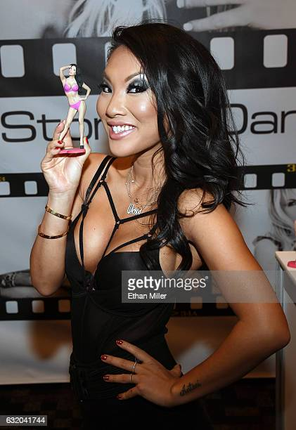 Adult film actress/director Asa Akira holds a Memento 3D Manufacture figurine of herself at the Wicked Pictures booth at the 2017 AVN Adult...