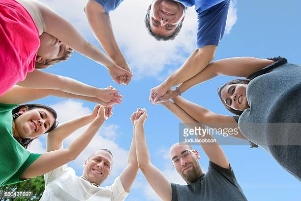 Adult friends and child huddled close together holding hands