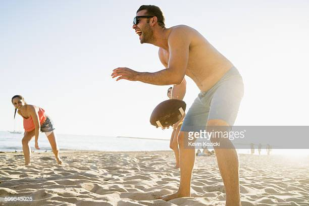 Adult friends playing American football on Newport Beach, California, USA