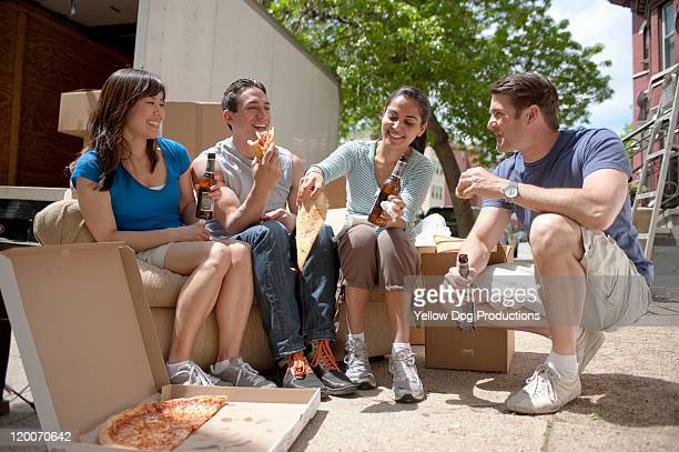 Adult friends taking a pizza break while moving