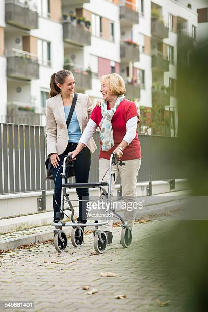 Adult granddaughter assisting her grandmother walking with wheeled walker