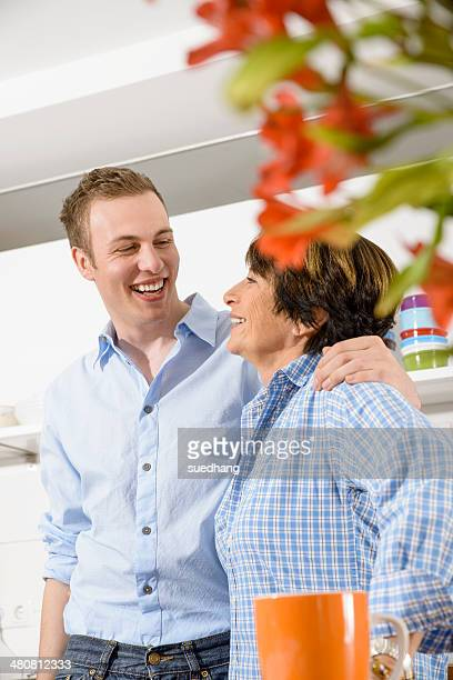 Adult grandson and grandmother in kitchen