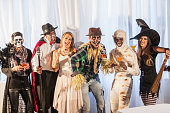 A multi-ethnic group of six men and women at an adult halloween party with alcoholic beverages.  The costumes include an vampire, angel, witch, scarecrow, mummy and zombie.