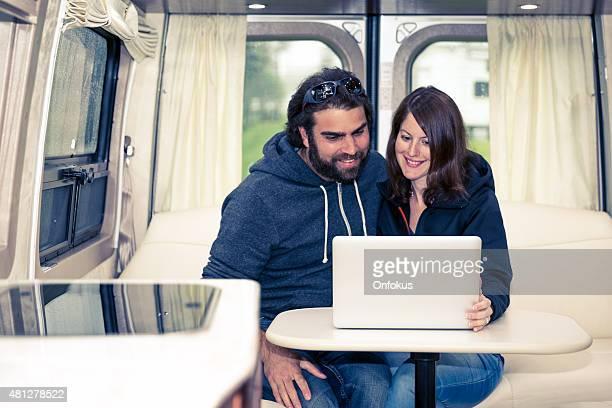 Adult Heterosexual Couple Using Laptop Inside Motorhome