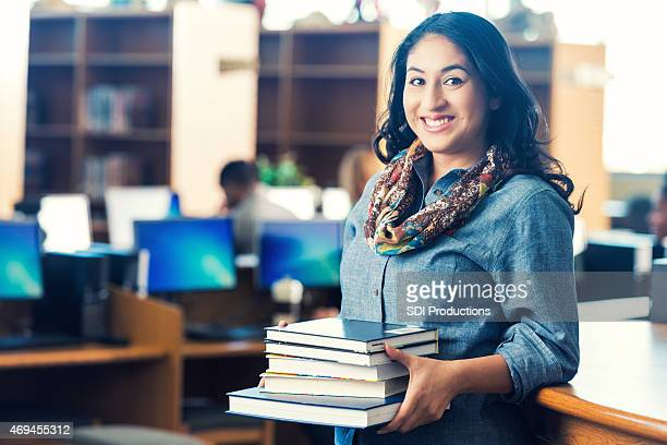Adult Hispanic student holding stack of books in college library
