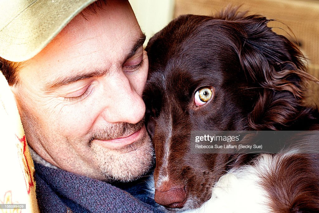 Adult male hugging the dog he loves : Stock Photo