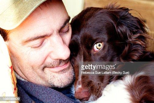 Adult male hugging the dog he loves : Foto de stock