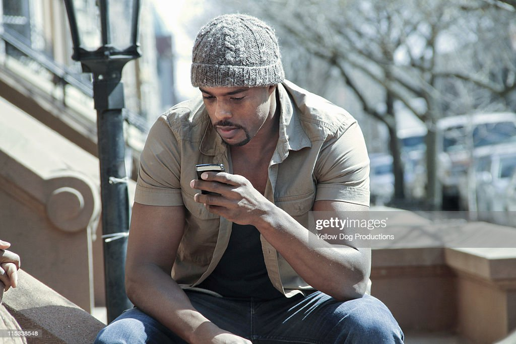 Adult Male on smart phone Sitting Outside Building : Stock Photo