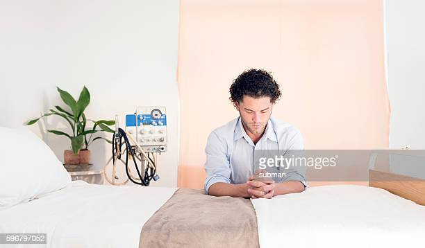 Adult Male Praying At Hospital Bed