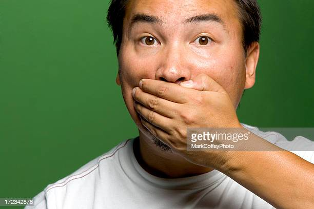 Adult male putting his hand over his mouth not speaking
