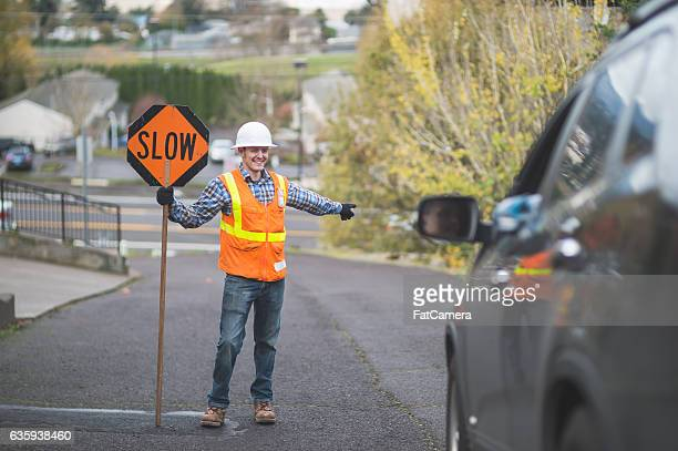 Adult male street flagger directing traffic