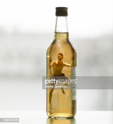 Adult male swimmer inside capped glass bottle