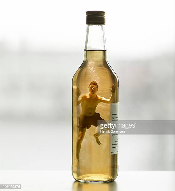 Adult male swimmer inside capped glass bottle