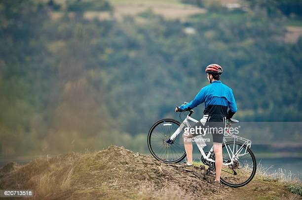 Adult male trail bike rider looking over valley