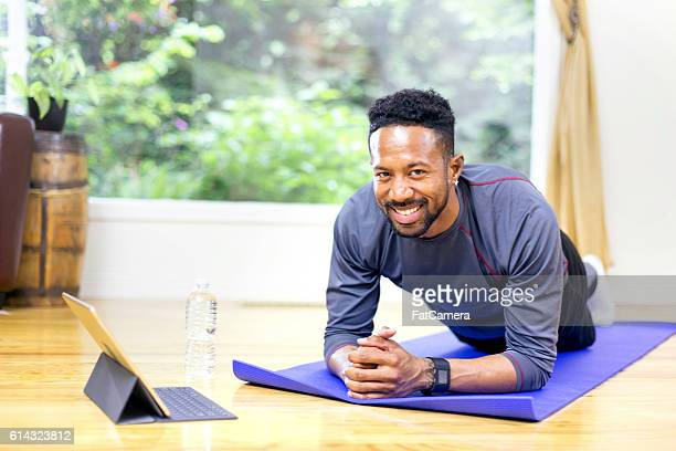 Adult male using smart tablet to guide workout and smiling