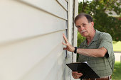 An adult male inspects residential vinyl siding.